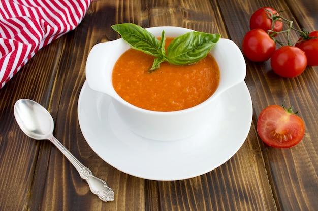 茶色の木製の背景に白いボウルにトマトスープ。クローズアップ。