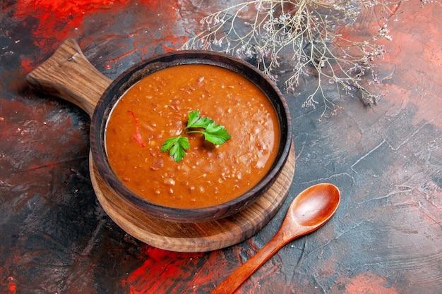 茶色のまな板にトマトスープ、混合色のテーブルにスプーン