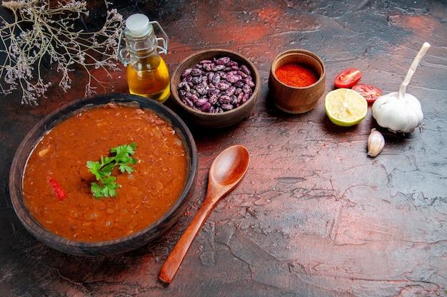 Zuppa di pomodoro pepe, aglio, limone e fagioli sulla tavola di colori misti