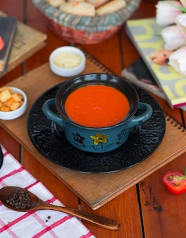 Tomato soup in a pot with chopped parmesan cheese and bread crackers
