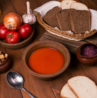 Tomato soup in pottery bowl served with vegetables and sliced brown bread.