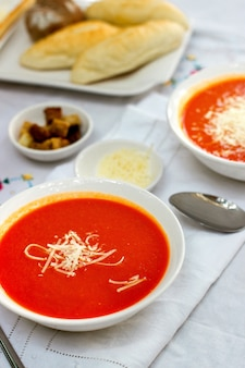 Tomato soup served with grated cheese and crackers