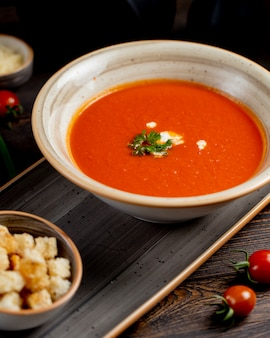 Tomato soup served with greens and crackers