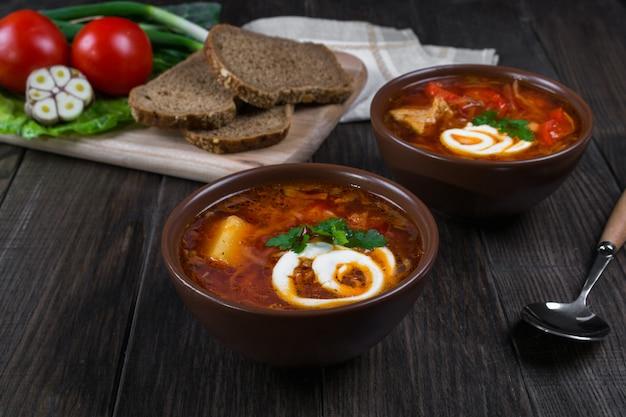 トマトスープ 。伝統的なウクライナビートの根とトマトのスープ-サワークリーム、ニンニク、ハーブ、暗い木製の表面にパンと土鍋でボルシチ。テーブルの上の食材