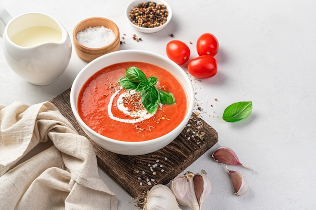 Tomato soup in a white bowl on a light background with ingredients