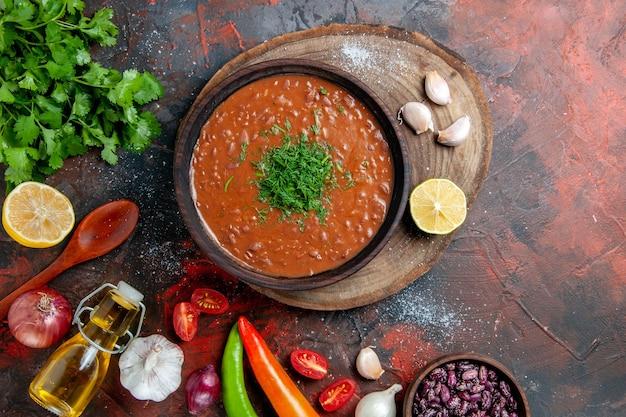 混合色のテーブルに緑のオイルボトルにんにくとスプーンの束とトマトスープ