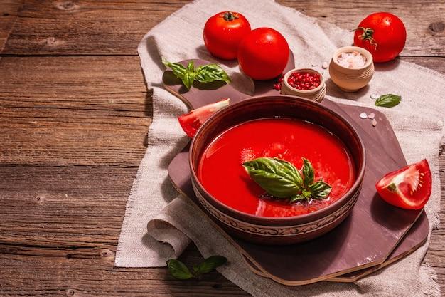 Томатный суп с базиликом в миске. спелые овощи, свежая зелень, ароматные специи. старинный деревянный стол, копия пространства