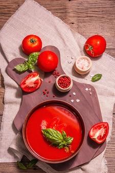 Томатный суп с базиликом в миске. спелые овощи, свежая зелень, ароматные специи. старинный деревянный стол, вид сверху