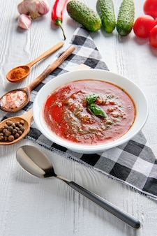 Tomato soup with basil, pepper, garlic and cucumber on wood