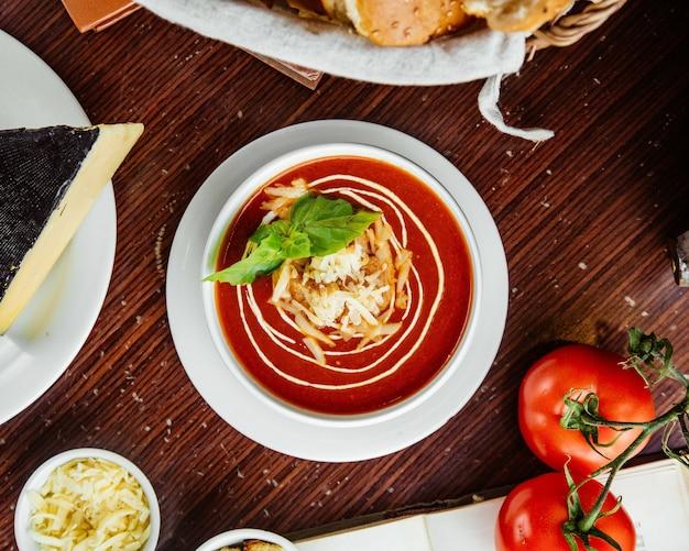 クラッカーとチーズトマトとパンのテーブルの上のトマトスープ