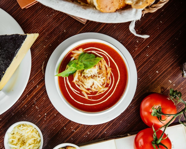 Tomato soup with crackers and cheese tomatoes and bread on the table