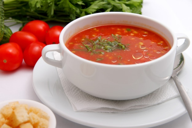 Tomato soup with crackers and herbs