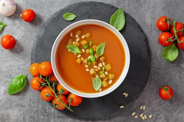 Томатный суп с гренками, свежей зеленью, базиликом и кедровыми орехами в миске на сером каменном фоне.