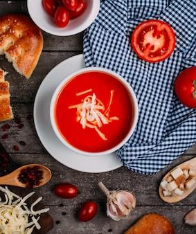 テーブルの上のすりおろしたチーズの上面とトマトのスープ