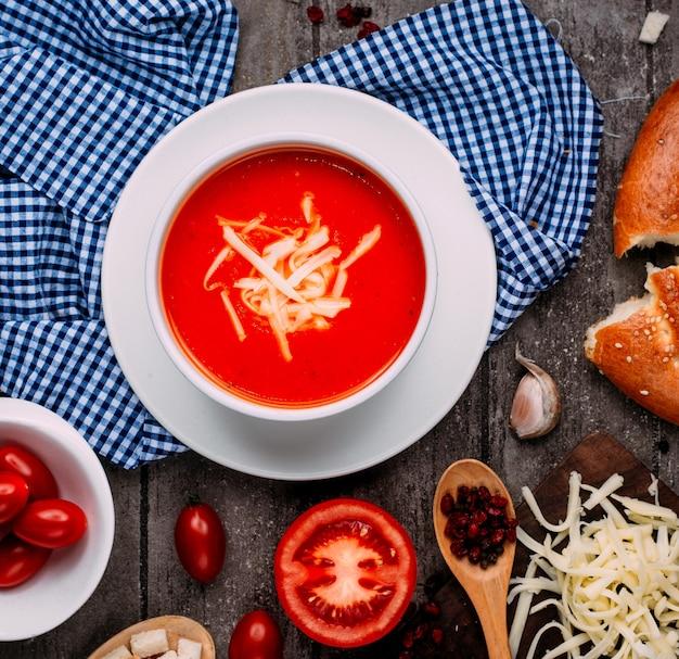Zuppa di pomodoro con vista dall'alto di formaggio grattugiato sul tavolo