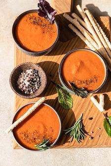 Томатный суп с молотым перцем, зеленью и гриссини прямой солнечный свет и жесткие тени