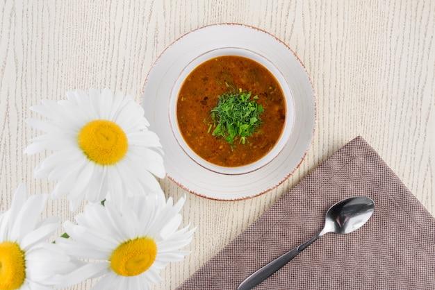 카모마일 꽃의 배경에 대해 가벼운 나무 테이블에 흰색 접시에 허브와 토마토 수프.