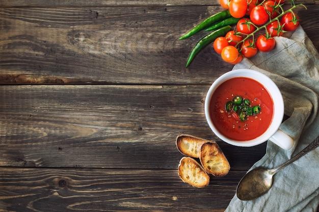 소박한 나무 배경에 할라피뇨 고추와 구운 빵을 곁들인 토마토 수프. 평면도.