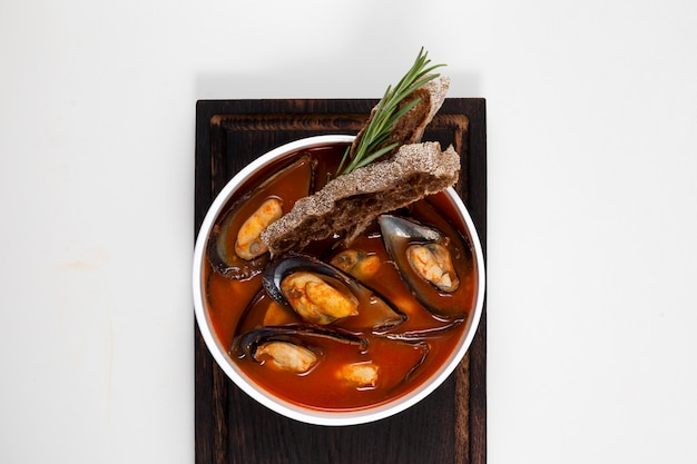 Tomato soup with mussels. served with rye croutons, garnished with a sprig of rosemary.
