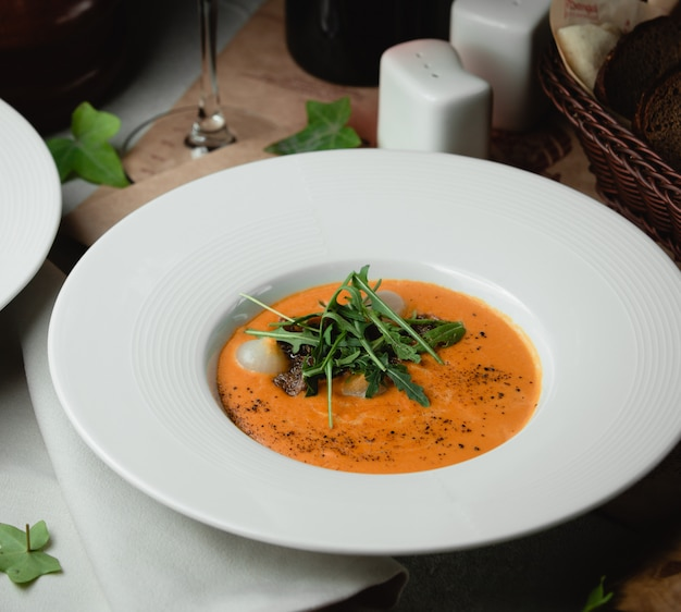 Tomato soup with onion and green herbs.