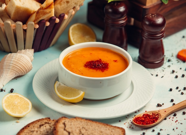 Tomato soup with paprika and lemon slices.
