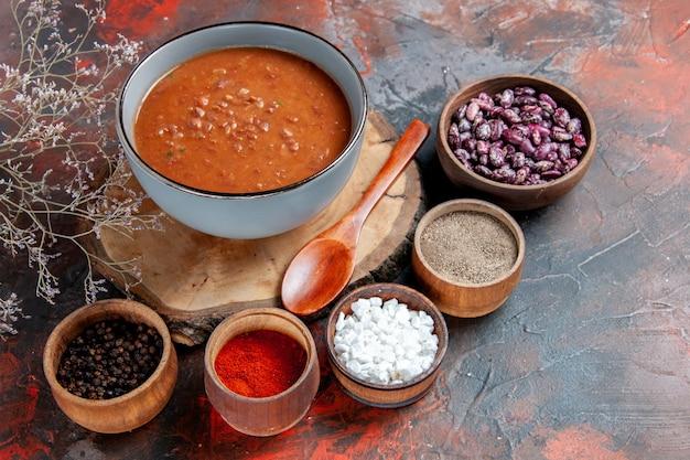 木製トレイ豆のスプーンと混合色のテーブルのさまざまなスパイスとトマトスープ