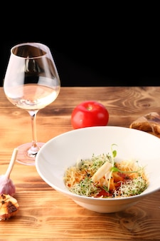 Tomato soup with squid and cheese decorated with microgreen on wooden table and white wine