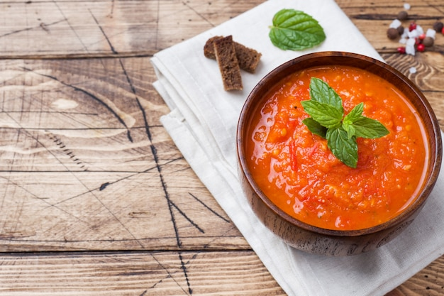 Tomato soup in a wooden bowl with pieces of toast on a rustic table