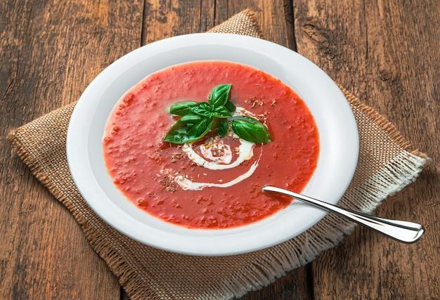 木製の背景にクリームと新鮮なバジルのトマトスーププリー