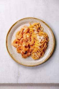 エビのエビのソースとパルメザンチーズのトマトスパゲッティパスタは、白い大理石の壁の上の斑点のあるセラミックプレートで提供されます。フラットレイ、コピースペース