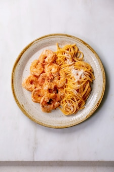 Tomato spaghetti pasta with shrimps prawns in sauce and parmesan cheese served in spotted ceramic plate over white marble wall. flat lay, copy space