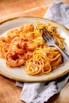 Tomato spaghetti pasta with shrimps prawns in sauce and parmesan cheese served in spotted ceramic plate with fork and cloth napkin over brown stone wall.
