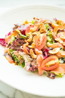 Tomato and vegetable salad with smoked salmon meat