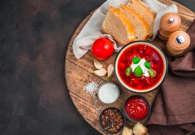 신선한 사워 크림과 함께 토마토 야채 수프. 갈색 콘크리트 배경에 전통적인 보르시입니다. 전통 요리의 개념.