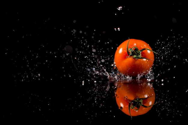 The tomato with drops stands on the black background