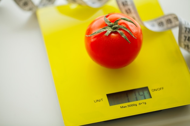 Tomato with measuring tape on weight scale