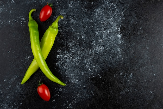 Tomatoe and chilli peppers on marble surface.
