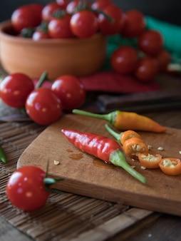まな板にトマトと唐辛子木製のまな板に唐辛子