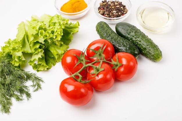 トマトとキュウリとスパイスは、料理の概念を白で隔離されます。食物 。
