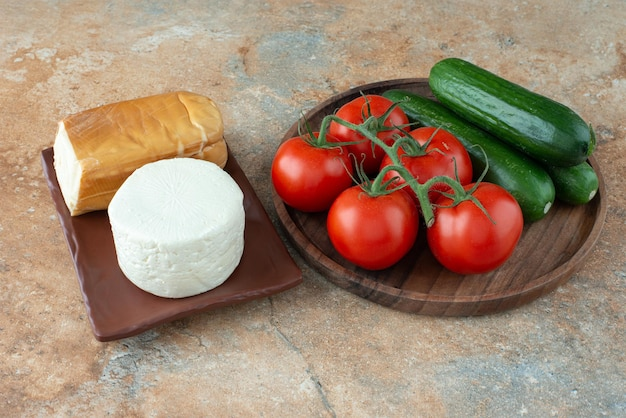 大理石のテーブルにチーズとトマトとキュウリ。