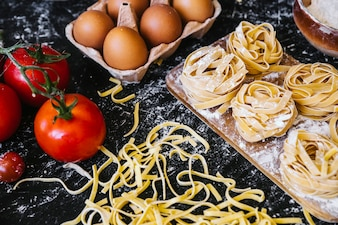 Tomatoes and eggs near pasta