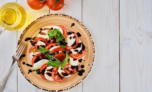 토마토와 모짜렐라-채식 요리, 토마토를 곁들인 이탈리아 카프레제 샐러드, 모짜렐라 치즈, 바질, 발사믹 식초 및 올리브 오일. 흰색 나무 테이블에 세라믹 플레이트입니다. 복사 공간이있는 평면도