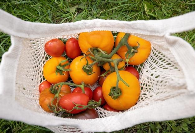 トマトは、草の背景に再利用可能なメッシュエコバッグに入った赤、黄、バーガンディです。