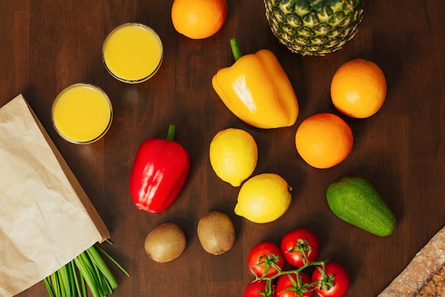 Tomatoes avocado green onions pepper kiwi ananas lemon orange and fresh juice on a dark wooden