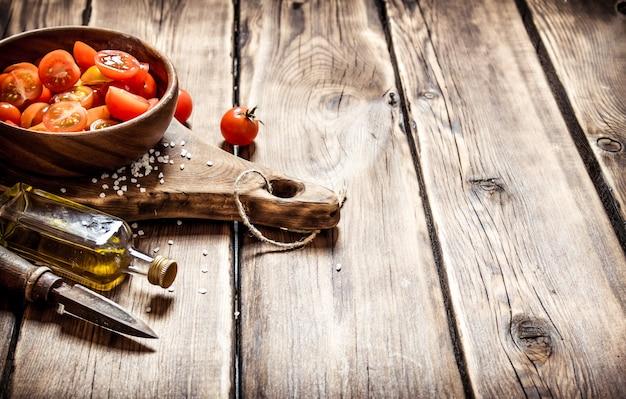 トマトの背景。オリーブオイルと木製のボウルにフレッシュトマト。木製の背景に。