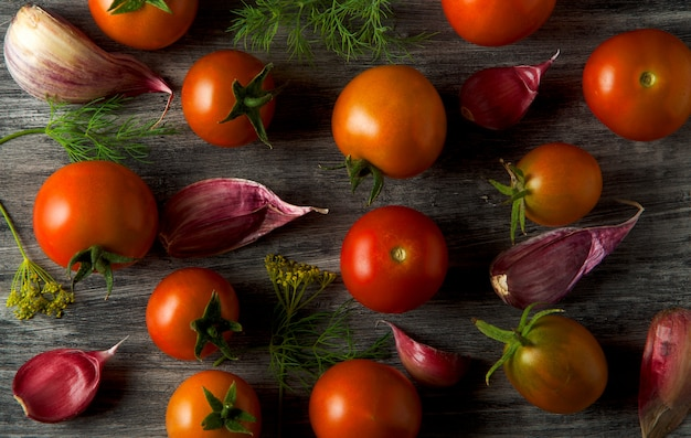 Tomatoes on the background. tomatoes, garlic on a wooden surface. view from above.
