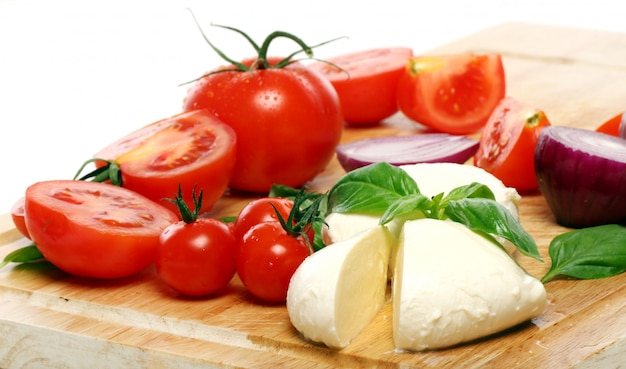 Tomatoes, basil and mozzarella on wooden board