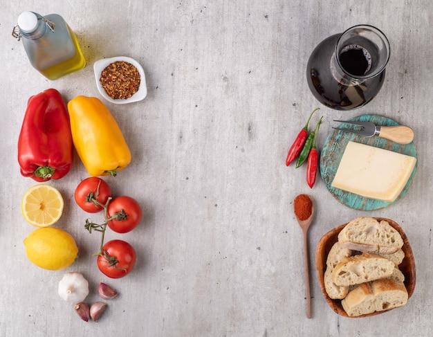 木製のテーブルの上にトマト、ピーマン、オリーブオイル、ナス、ニンニク。コピースペースのある地中海料理。
