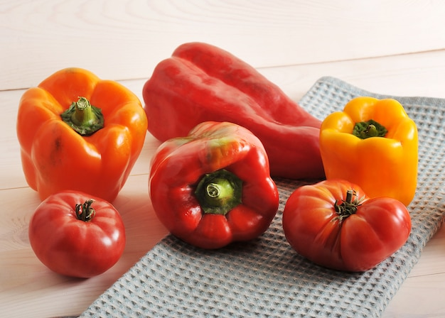 Tomatoes and bell peppers on wooden surface