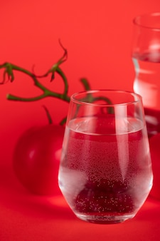 Tomatoes on branches with glasses of water